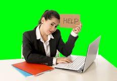 Donna di affari che lavora al suo computer portatile che giudica un segno di aiuto isolato sulla chiave verde di intensità immagine stock libera da diritti