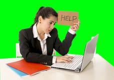 Donna di affari che lavora al suo computer portatile che giudica un segno di aiuto isolato sulla chiave verde di intensità immagine stock