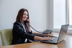 Donna di affari che lavora al suo computer portatile e che parla sul telefono immagini stock