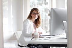 Donna di affari che lavora all'ufficio fotografie stock