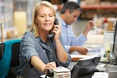 Donna di affari che lavora allo scrittorio in magazzino Fotografia Stock Libera da Diritti