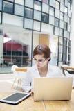Donna di affari che lavora con il computer portatile e il ipad Immagini Stock Libere da Diritti