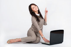 Donna di affari che lavora con il computer portatile e le manifestazioni il gesto immagini stock