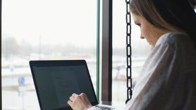 Donna di affari che lavora con il computer portatile e che parla sul telefono cellulare stock footage