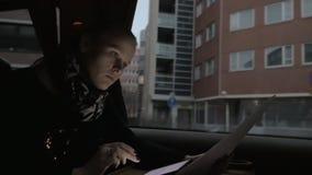 Donna di affari che lavora con la compressa digitale ed i documenti in treno video d archivio