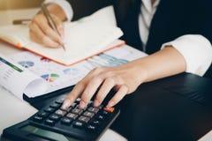 Donna di affari che lavora con la mano di dati finanziari facendo uso del calcolatore immagini stock libere da diritti