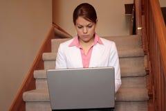 Donna di affari che lavora nel paese sul suo computer portatile Immagine Stock