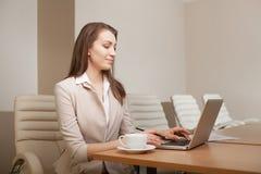 Donna di affari che lavora nell'ufficio e che per mezzo del computer portatile Fotografie Stock Libere da Diritti