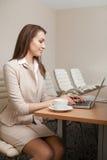 Donna di affari che lavora nell'ufficio e che per mezzo del computer portatile Immagini Stock Libere da Diritti