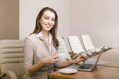 Donna di affari che lavora nell'ufficio e che per mezzo del computer portatile Immagini Stock