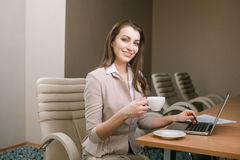 Donna di affari che lavora nell'ufficio e che per mezzo del computer portatile Fotografia Stock