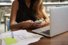 Donna di affari che lavora nell'ufficio facendo uso del telefono, metà di sezione immagini stock