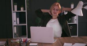 Donna di affari che lavora tardi e che allunga all'ufficio stock footage
