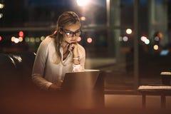 Donna di affari che lavora tardi sul computer portatile immagini stock