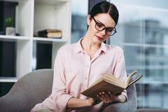 Donna di affari che legge il libro fotografie stock