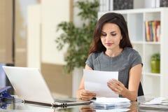 Donna di affari che legge una lettera all'ufficio Fotografia Stock Libera da Diritti