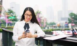 Donna di affari che manda un sms nell'ambiente moderno Fotografia Stock