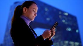 Donna di affari che manda un sms in telefono cellulare contro il paesaggio urbano moderno video d archivio