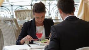 Donna di affari che mangia con un uomo d'affari stock footage