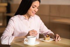 Donna di affari che mangia dolce con caffè immagini stock