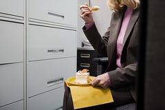 Donna di affari che mangia dolce nel segreto Fotografie Stock Libere da Diritti