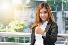 Donna di affari che mostra pollice sul gesto, fondo della città immagini stock