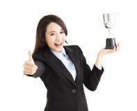 Donna di affari che mostra trofeo e pollice su fotografie stock libere da diritti