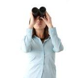 Donna di affari che osserva con binoculare Immagine Stock