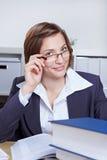 Donna di affari che osserva sopra l'orlo dei suoi vetri Immagini Stock Libere da Diritti