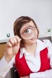 Donna di affari che osserva tramite la lente d'ingrandimento Fotografia Stock