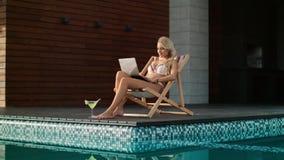 Donna di affari che ottiene sunbath vicino alla piscina Computer funzionante della donna sexy video d archivio