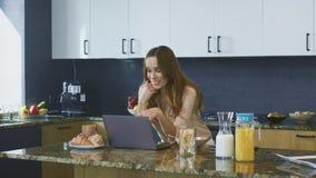 Donna di affari che parla al computer in cucina Signora di sorriso del primo piano che ha chiacchierata archivi video