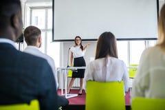 Donna di affari che parla alla conferenza Pubblico al corridoio di conferenza Multi società etnica immagine stock