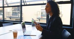 Donna di affari che parla sul telefono cellulare mentre per mezzo del computer portatile 4k video d archivio