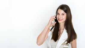 Donna di affari che parla sul telefono contro un fondo bianco fotografie stock