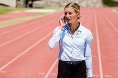 Donna di affari che parla sul telefono su una pista corrente Fotografia Stock Libera da Diritti