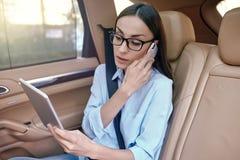 Donna di affari che parla sullo smartphone nell'automobile immagine stock