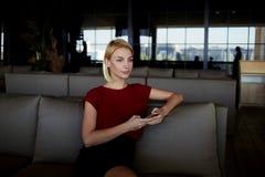 Donna di affari che pensa al giorno del lavoro di domani mentre sedendosi con lo Smart Phone in ristorante moderno, Fotografia Stock