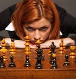 Donna di affari che pensa alla sua prossima tappa in un gioco di scacchi Immagini Stock Libere da Diritti