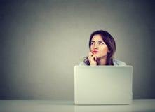 Donna di affari che pensa fantasticando seduta allo scrittorio con il computer portatile Immagine Stock Libera da Diritti