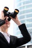 Donna di affari che per mezzo del binocolo Fotografia Stock