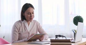 Donna di affari che per mezzo del blocco note mentre avendo videoconferenza sul computer portatile archivi video