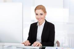 Donna di affari che per mezzo del calcolatore Immagine Stock