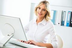 Donna di affari che per mezzo del calcolatore all'ufficio Fotografia Stock Libera da Diritti
