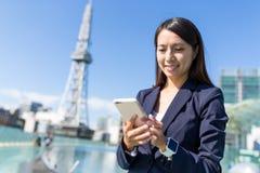 Donna di affari che per mezzo del cellulare alla città di Nagoya immagine stock