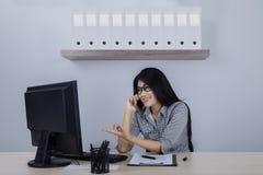Donna di affari che per mezzo del computer e del telefono Immagine Stock Libera da Diritti