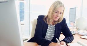 Donna di affari che per mezzo del computer e prendendo le note video d archivio