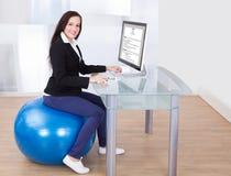 Donna di affari che per mezzo del computer mentre sedendosi sulla palla dei pilates Immagine Stock