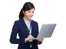 Donna di affari che per mezzo del computer portatile Fotografia Stock