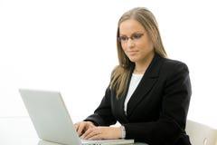 Donna di affari che per mezzo del computer portatile allo scrittorio Fotografie Stock Libere da Diritti